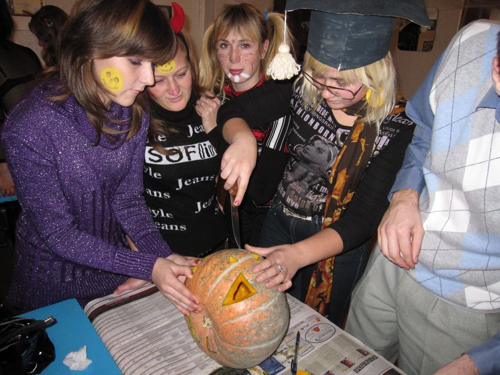 Oxsana, Oxana, Luba, and Sasha work hard on their pumpkin.