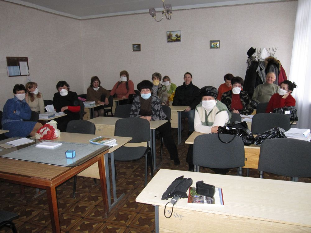 Teachers donning their protective masks in the teacher's lounge.